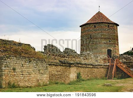 Watchtower, walls, arched windows and the pointed conical roof of Fortress Akkerman in the morning mist Bilhorod-Dnistrovskyi, Ukraine. View from inner courtyard