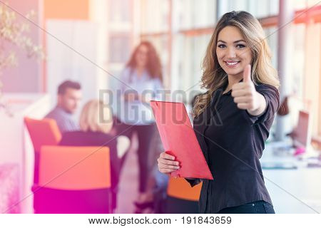 portrait of young business woman at modern startup office interior showing thumbs up.