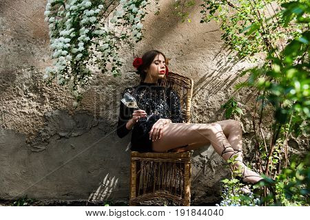 Pretty Girl With Closed Eyes And Glass Sitting On Chair