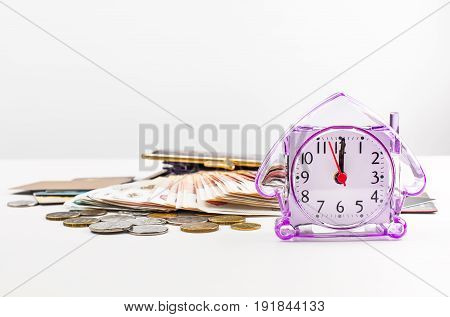 Banknotes coins watch purse and credit cards.