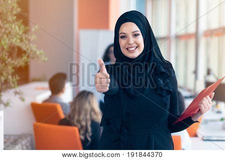 Arabian business woman with hijab holding a folder.