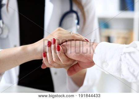 Friendly Female Doctor Hold Male Patient Hand In Office