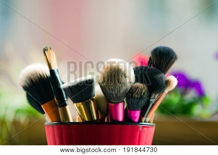 brush for fashionable makeup or cosmetic in pink cup on blurred background fashion and beauty visage and design