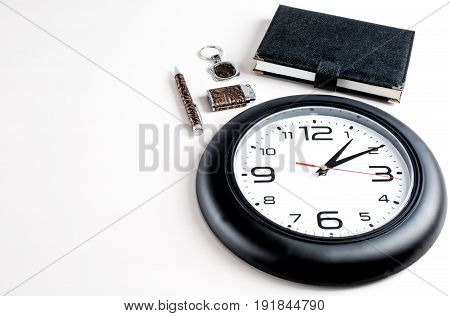 Collage. Lighter key chain notepad and pen are located next to the clock. White background.