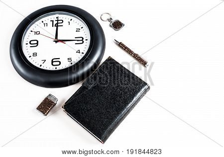 Collage. Notepad pen lighter and key chain are located next to the clock. White background.