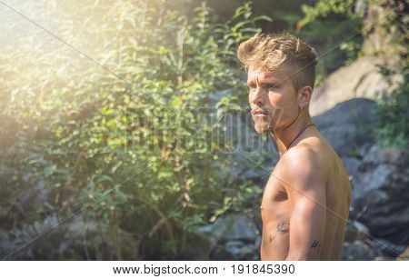 Half body shot of shirtless blond young man's profile, alone in nature, looking to a side