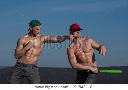 young people of men with baseball bat in hand on sky background spring and summer nature energy
