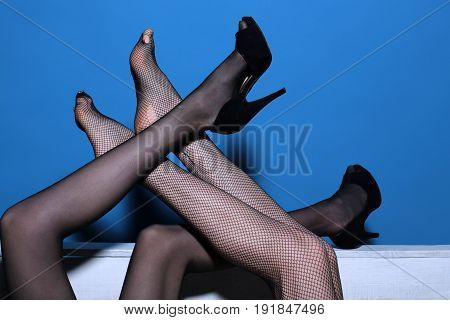 sexy legs of women in fashionable tights and shoes mixed on wooden bench on blue background couple in love lesbian