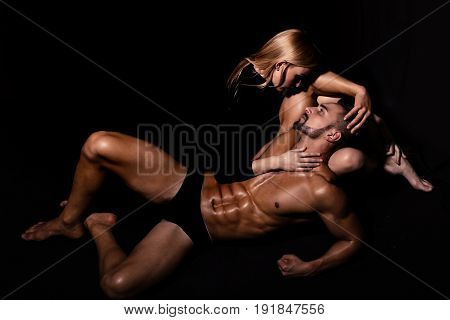 couple in love of man with muscular wet body and strong athletic torso with sexy blonde girl in underwear pants on black background love relations