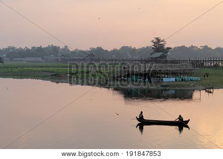 U-BEIN BRIDGE/AMARAPURA, MYANMAR JAN 22: Two fishermen in their canoe like boat head out for work as the sun is rising over  Taungthaman Lake. January 22, 2016, U-Bein bridge/Amarapura.