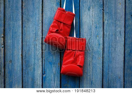 pair of red gloves for kickboxing hanging on a white rope a blue cracked wooden background