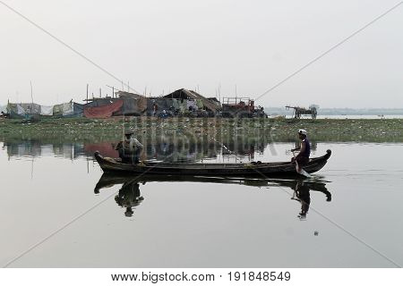 U-BEIN BRIDGE/AMARAPURA, MYANMAR JAN 22: Two fishermen on Taungthaman Lake heading out for work in their boat in the early morning hours January 22, 2016, U-Bein bridge/Amarapura.