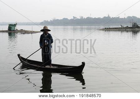 U-BEIN BRIDGE/AMARAPURA, MYANMAR JAN 22: A woman is navigating her boat on the Taungthaman Lake that is being crossed by the famous  bridge made entirely of teak wood.January 22, 2016, U-Bein bridge/Amarapura.