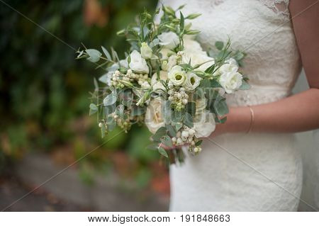 Beautiful bridal modern bouquet in the hands of the bride.