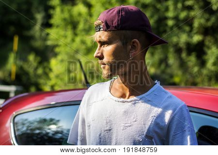 Portrait of young attractive blond man with baseball cap and white t-shirt, next to his new stylish car outdoor in countryside