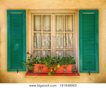 rustic window with old green shutters and flower pot in stone rural house