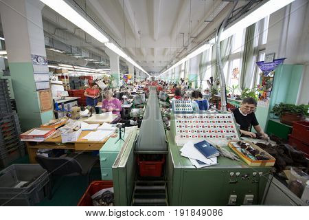 MOSCOW - FEB 21, 2017: Working people near transporter in workshop of Ralf Ringer factory. In 1995 Ralf Ringer started manufacturing its own shoes