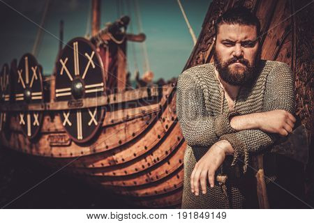 Viking with axe standing near drakkar on the seashore.