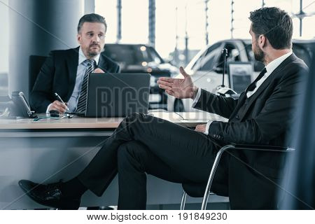 Top sales manager and customer at dealership showroom