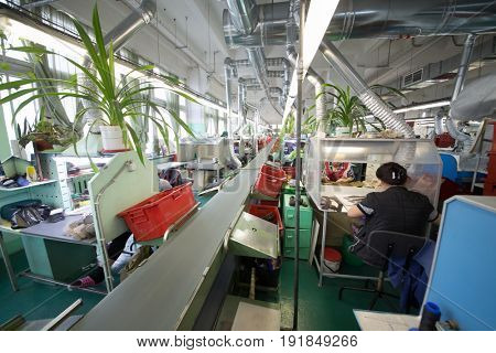 MOSCOW - FEB 21, 2017: Workers near conveyor in workshop of Ralf Ringer factory. In 1995 Ralf Ringer started manufacturing its own shoes