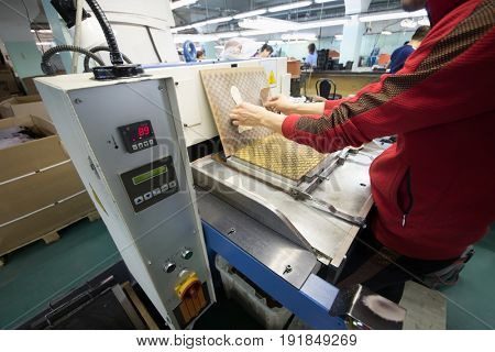 MOSCOW - FEB 21, 2017: Man puts logos on leather before cutting in workshop in Ralf Ringer factory. Company production is 1,5 million pairs per year