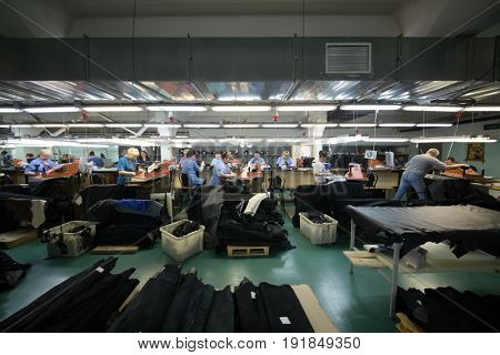 MOSCOW - FEB 21, 2017: Workers in workshop with leather and suede cutting machines in Ralf Ringer factory. Company production is 1,5 million pairs per year