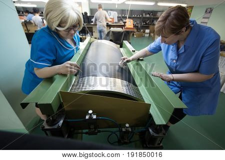 MOSCOW - FEB 21, 2017: Two women marking before cutting leather in workshop in Ralf Ringer factory. Company production is 1,5 million pairs per year