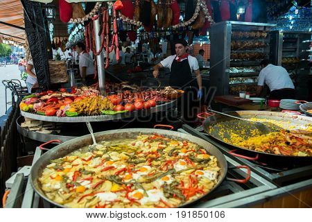 Street food in San Fermin feast, Pamlona, Navarra, Spain. 06 July 2016. Paella. Rise with seafood and vegetables. Spanish traditional cuisine. Spanish national dish, image toned and noise added.