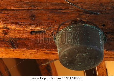 Old rusty copper pot hanging in a girder