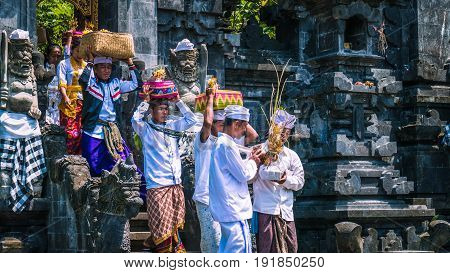 GOA LAWAH, BALI, INDONESIA - November 3, 2016: Balinese people in traditional clothes carry bless gift after ceremony at Pura Goa Lawah temple, Bali, Indonesia.
