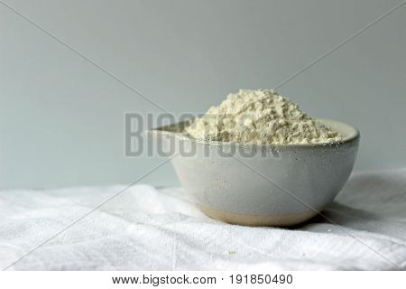 A pottery bowl with heaping white flour on linen. Copy space.