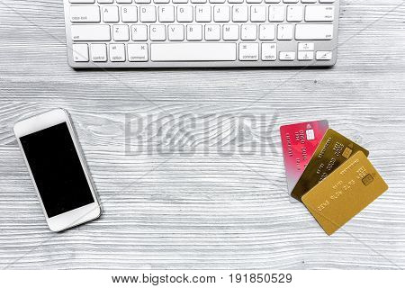 mobile, keyboard and credit cards for online purchasing on gray desk background top view mockup