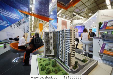 MOSCOW - MAR 16, 2017: Miniature of tall building and people at real estate exhibition in Central House of Artists, 200 companies took part in exhibition
