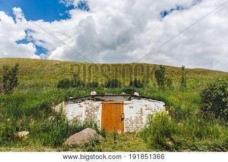 Dugout in a green hill, a wooden door, a hobbits' home
