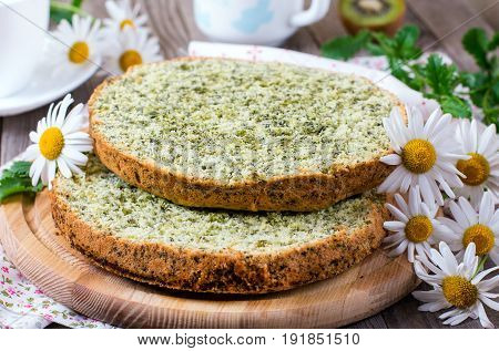 Sponge cake with spinach on a wooden background