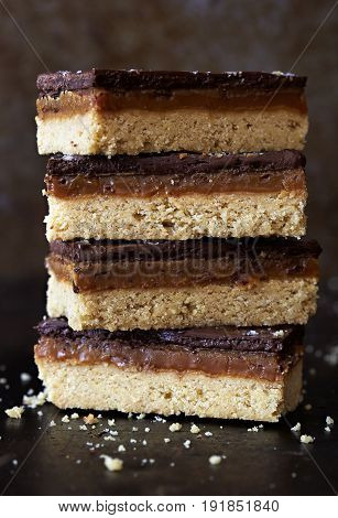 Salted caramel chocolate shortbreads stacked on dark background
