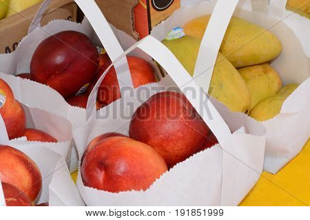 Organic apples and mangoes in white paper bags at farmer's market