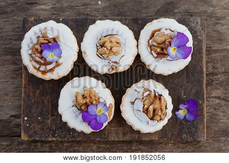 Top view of shortbread cake with walnut and edible flowers