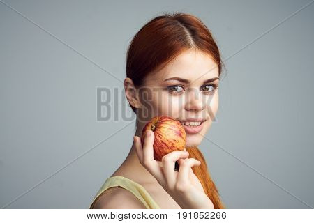 Woman with apple, diet, healthy eating, woman holding apple on gray background.