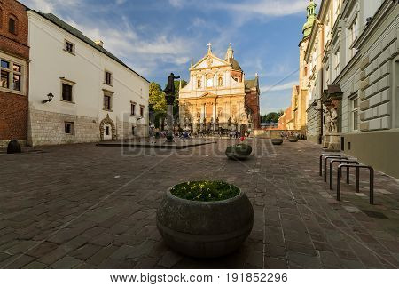 Square with monument and church in Krakow Poland in the evening. Europe.