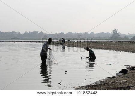 U-BEIN BRIDGE/AMARAPURA, MYANMAR JAN 22:  Two fishermen on Taungthaman Lake are setting out their net before sunrise January 22, 2016, U-Bein bridge/Amarapura.