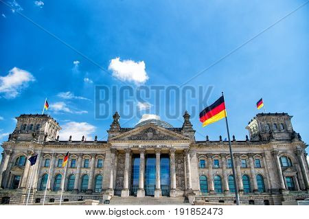 German flags waving in the wind at famous Reichstag building seat of the German Parliament (Deutscher Bundestag) on a sunny day with blue sky and clouds central Berlin Mitte district Germany
