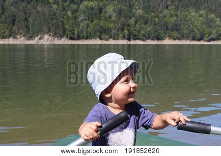 a small boy rowing a boat in the middle of the river. child enjoys boating and canoeing. small kid boy like fishing