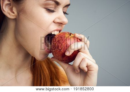 Woman biting an apple, healthy diet, diet, woman with an apple on a gray background.
