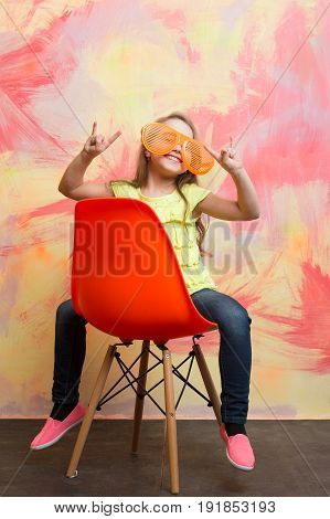 Little Happy Girl Wearing Yellow Tshirt And Glasses On Chair