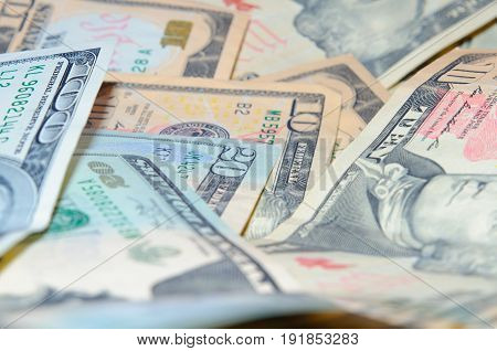 Scattered banknotes of ten twenty and one hundred dollars
