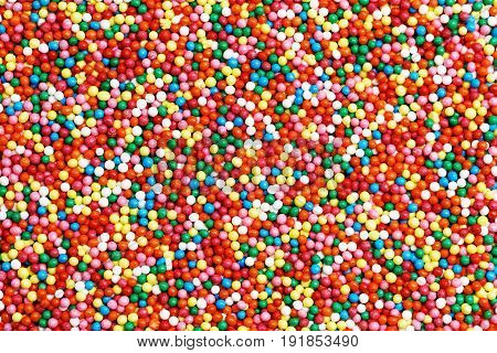 Background of colorful round-shaped candies filled with chocolate, heap of multi-colored balls. Top view.