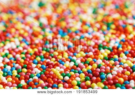 Background of colorful round-shaped candies filled with chocolate, heap of multi-colored balls. Angle view. Shallow focus.