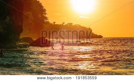 Sunset on beautiful Crystal Bay, Warm coloured sun flares reflection, Nusa Penida, Bali, Indonesia.