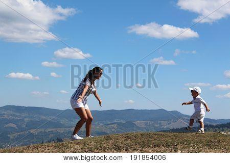 a little son with mother on the field and hills. a small boy runs  towards his mum. they are dressed total white. family has fun on travel in the mountains.
